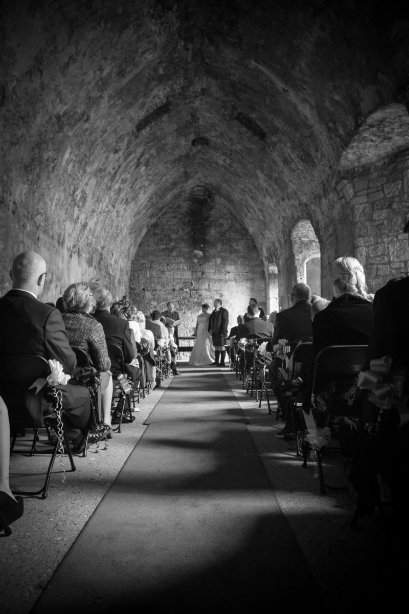Atmospheric wedding ceremony candid in Inchcolm Abbey