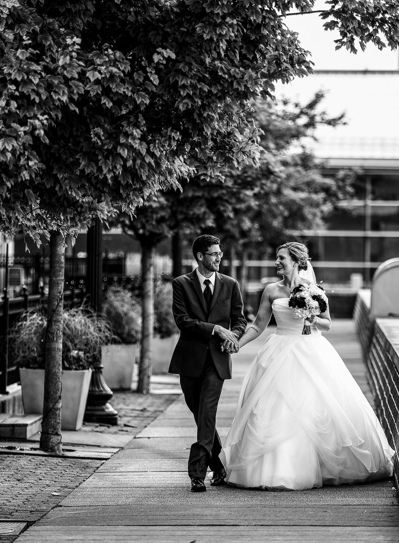 Bride and groom walking the path outside the Sheraton Erie Bayfront Hotel