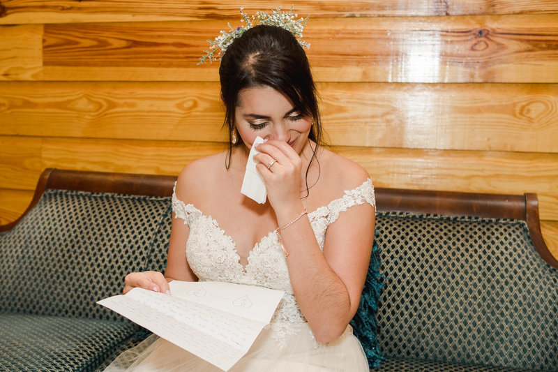 Bride getting emotional while reading groom's letter at Club Lake Plantation Wedding