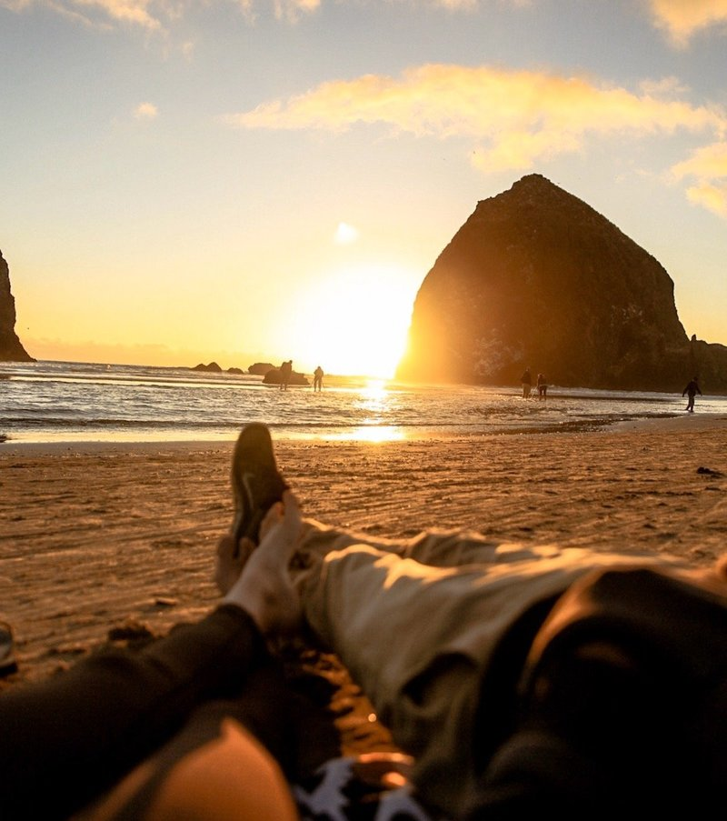 photo of bree and stephen laying on the beach on the west coast