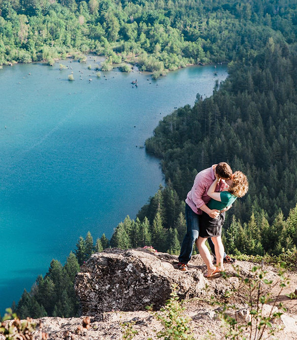 a couple kisses on top of a mountain on Rattlesnake Ledge on a hot summer afternoon during their hiking engagement session with adventure wedding photographer Amy Galbraith