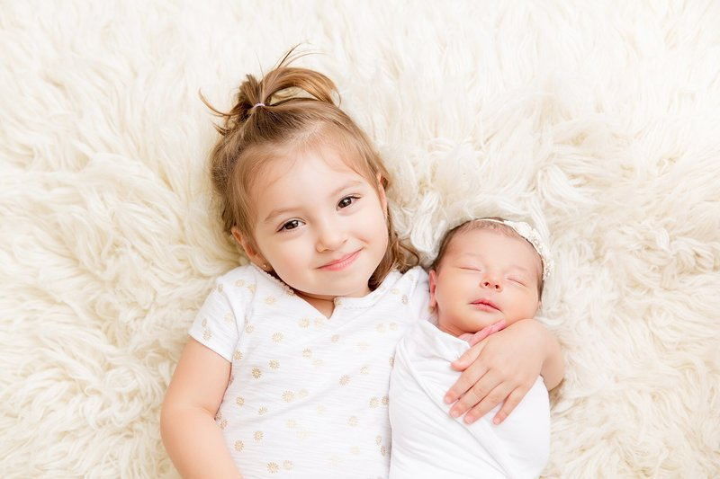 Sibling girl with newborn sister
