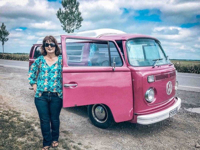Lynda standing beside kombi van Pippi on roadside in Canterbury, New Zealand on a road tirp.