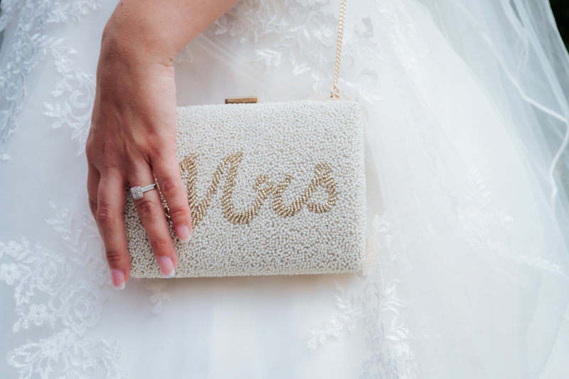 "close up photo of a bride's handbag.  The handbag is resting on top of her wedding dress and is embellished with beads which spell ""mrs"".  Her hand with wedding rings showing rests on her handbag."