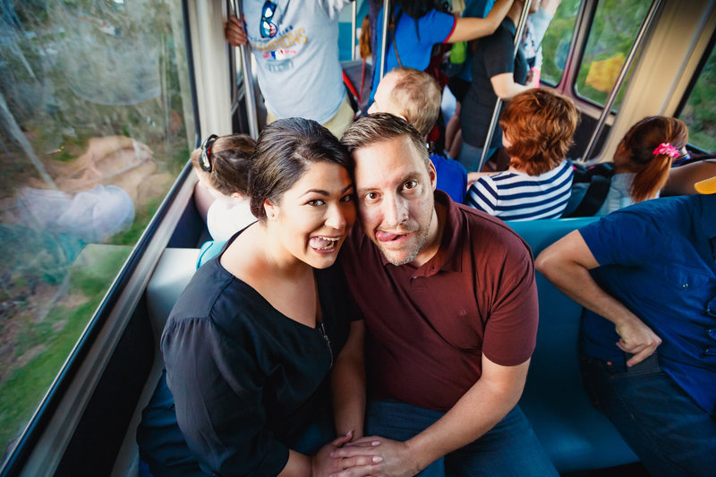 Couple Seated on a Crowded Shuttle Leans in and Sticks their Tongues Out During their Disney Engagement Photo Session