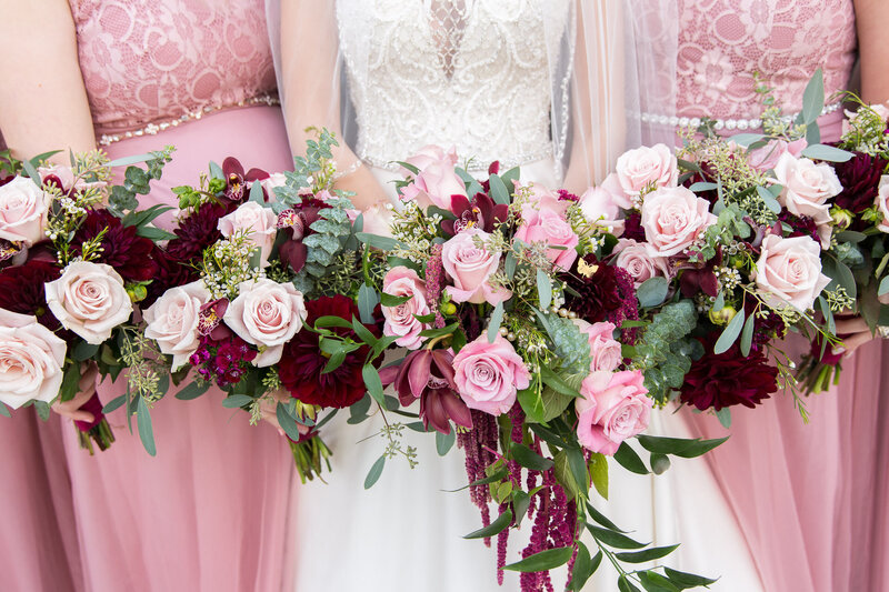 pink and red rose bouquets with pink bridesmaids dresses