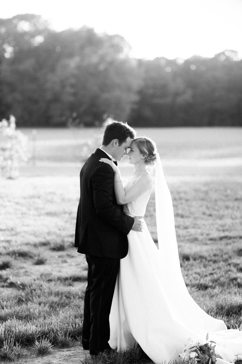 Black and white portrait of a bride and groom at sunset on the river in Virginia