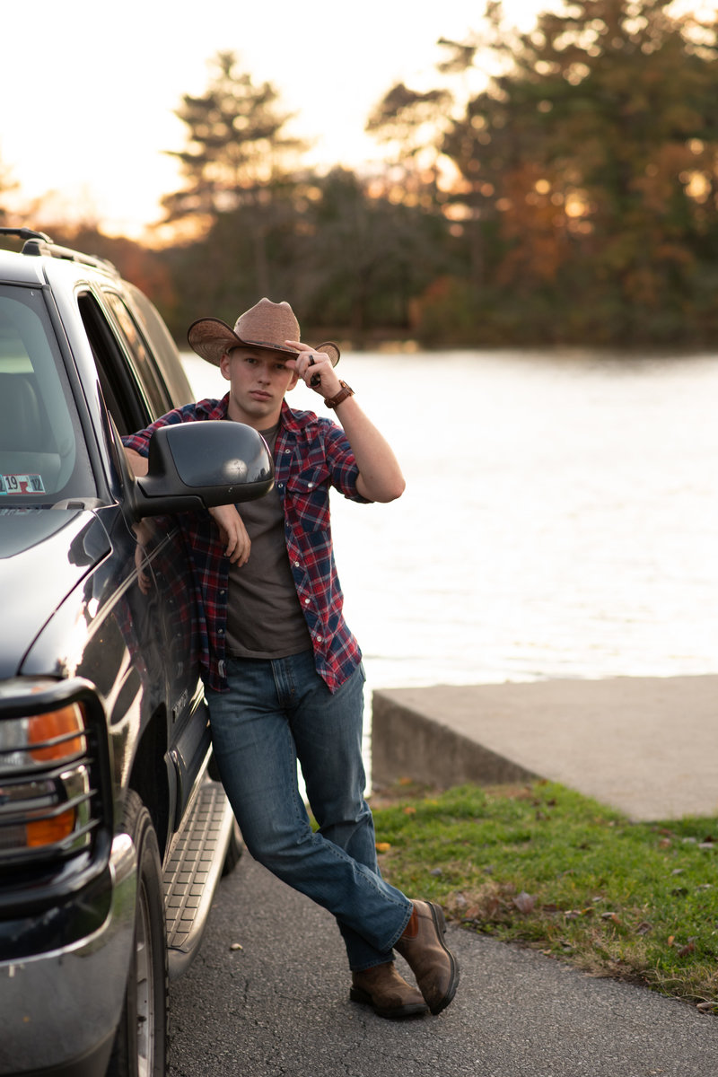Senior guy in western wear leaning on truck