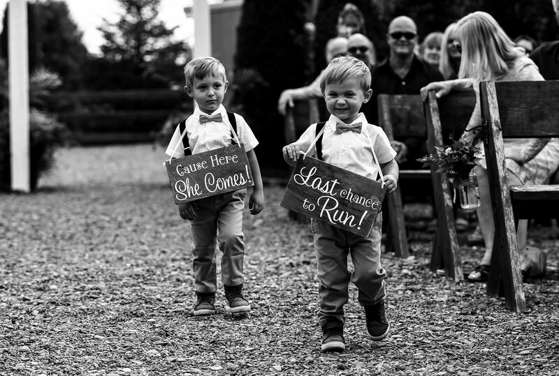 Ring bearers wearing cute signs walk down the aisle before the bride
