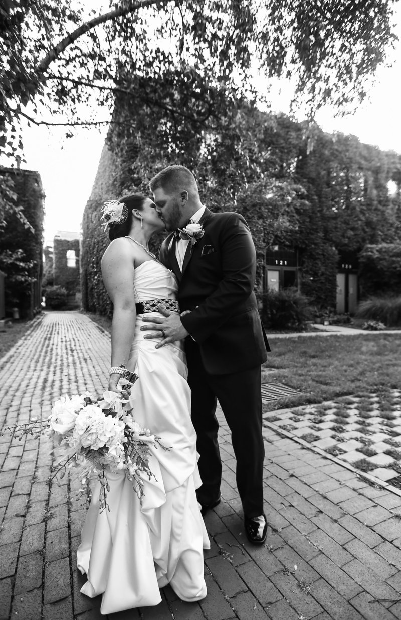 Bride and groom kiss in courtyard in downtown Erie, PA