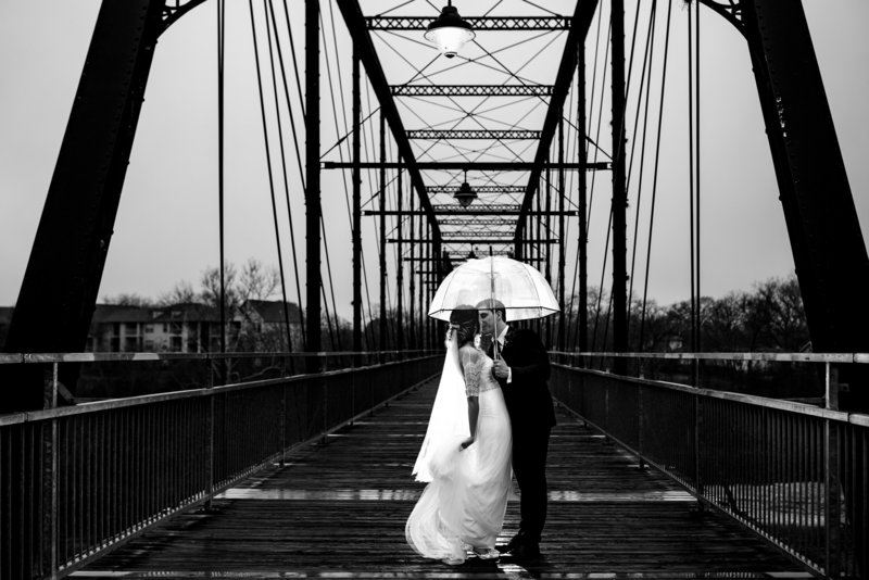Bride and groom on wedding day at Milltown Historic District in New Braunfels, TX.  Standing on Faust Bridge