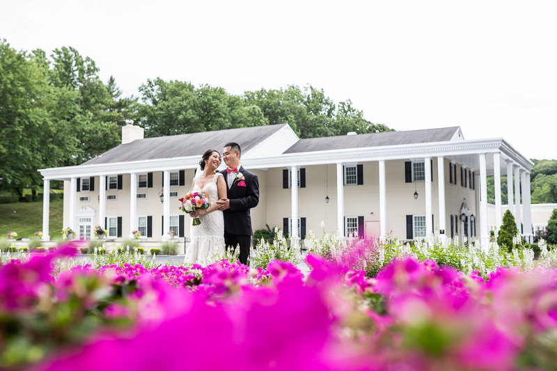 Bride and groom standing in front of Drexelbrook in the summer