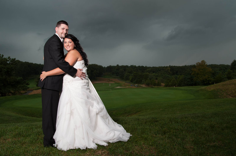 bride and groom under stormy skies
