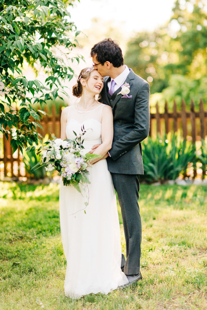 groom kisses bride on forehead in a sunlit garden