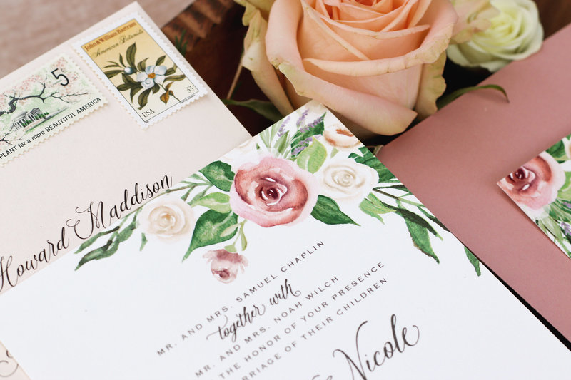 Close up shot: An elegant floral wedding invitation featuring hand-painted watercolor roses, lavender and beautiful flowing greenery.