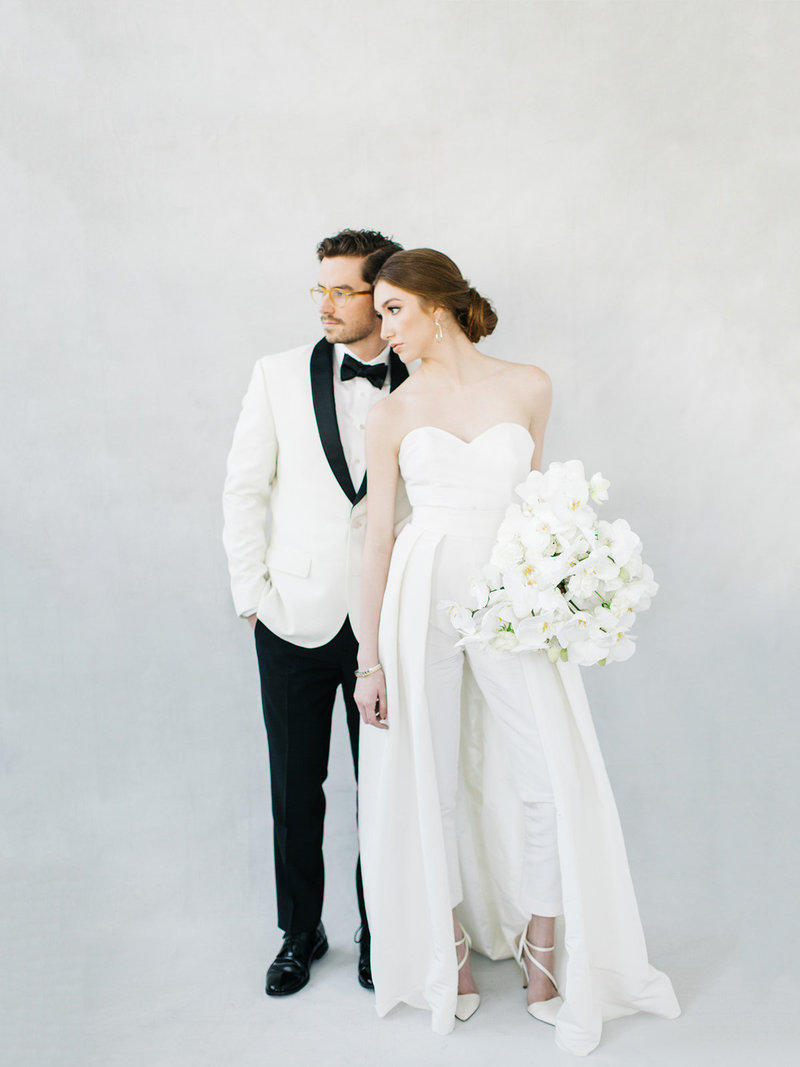 A destination wedding couple in wedding dress with removable cape and dinner jacket