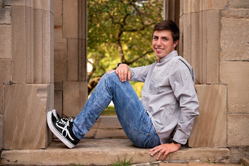 High school senior boy seated in archway of stone mansion at Hartwood Acres in Pittsburgh, PA
