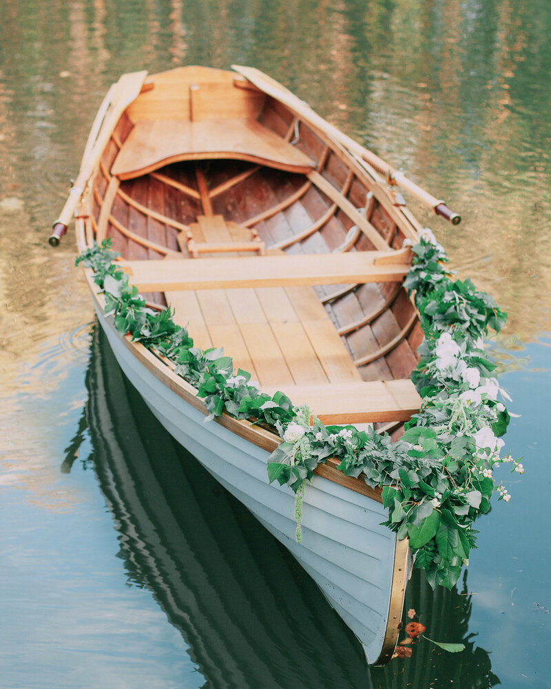 A quaint rowing boat adorned with wedding flowers for a luxury proposal on a lake.