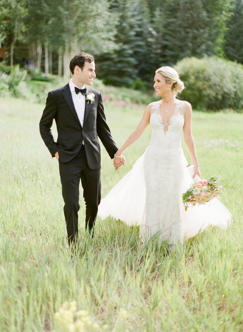 Testimonial photo, a bride and groom hold hands while looking at each other in tall grass