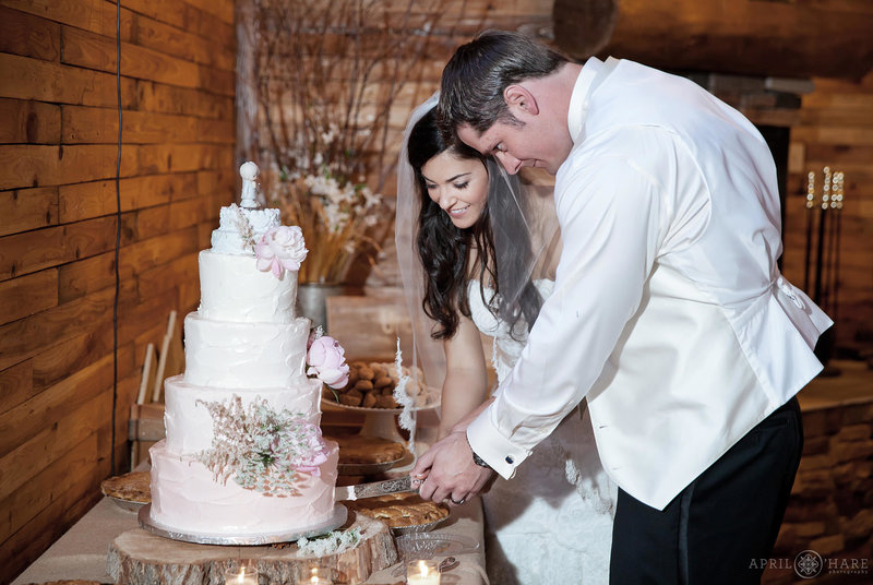 Cake cutting inside barn at Mountain View Ranch wedding reception