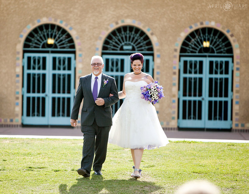 Bride walks with her dad to outdoor City Park Pavilion Wedding in Denver on a hot summer day