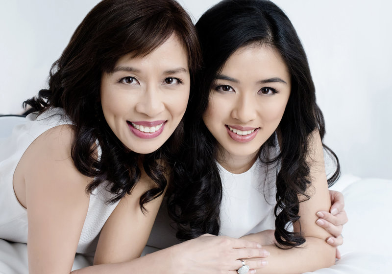 mother and  daughter pose together beautiful smile with clear smooth skin asian mother  with long black  hair