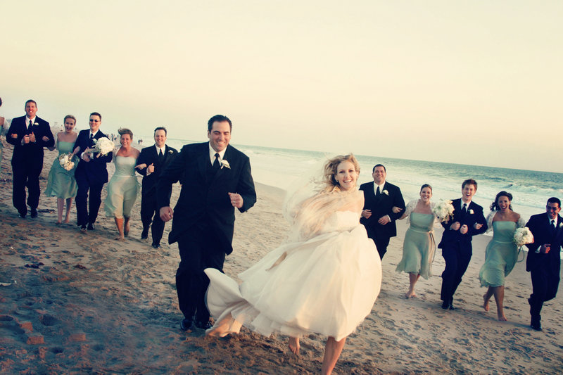 bridal party running on beach