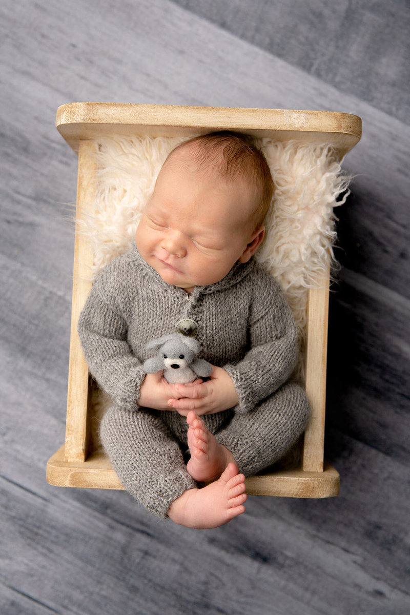 newborn boy dressed in grey smiles holding a teddy in a crib