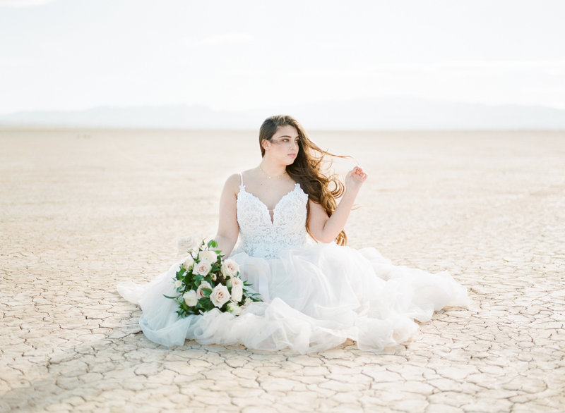 Beautiful bride in wedding gown sets in desert with bouquet