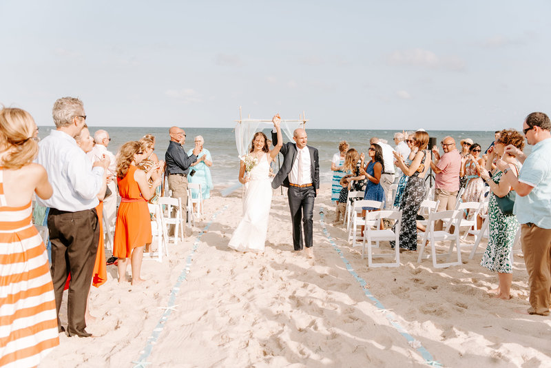 bride and groom share their joy after beach wedding ceremony