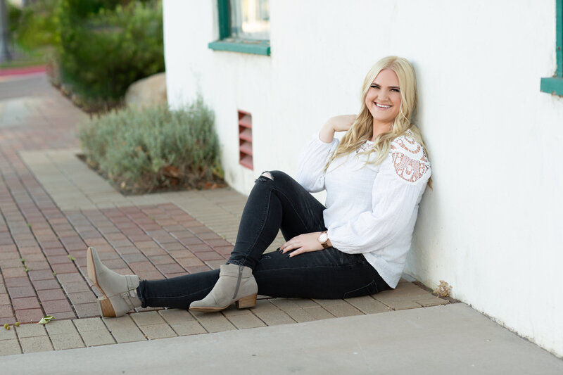 EMDR Therapist Megan Zuzevich sits with her back against a stone wall, with legs crossed looking comfortable and approachable for trauma therapy and PTSD treatment for EMDR therapy in California