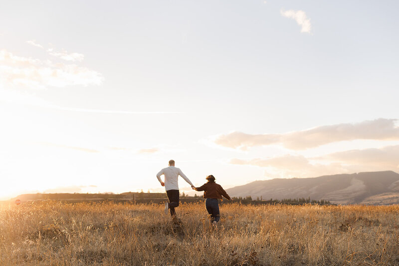 couple running through field in rowena oregon
