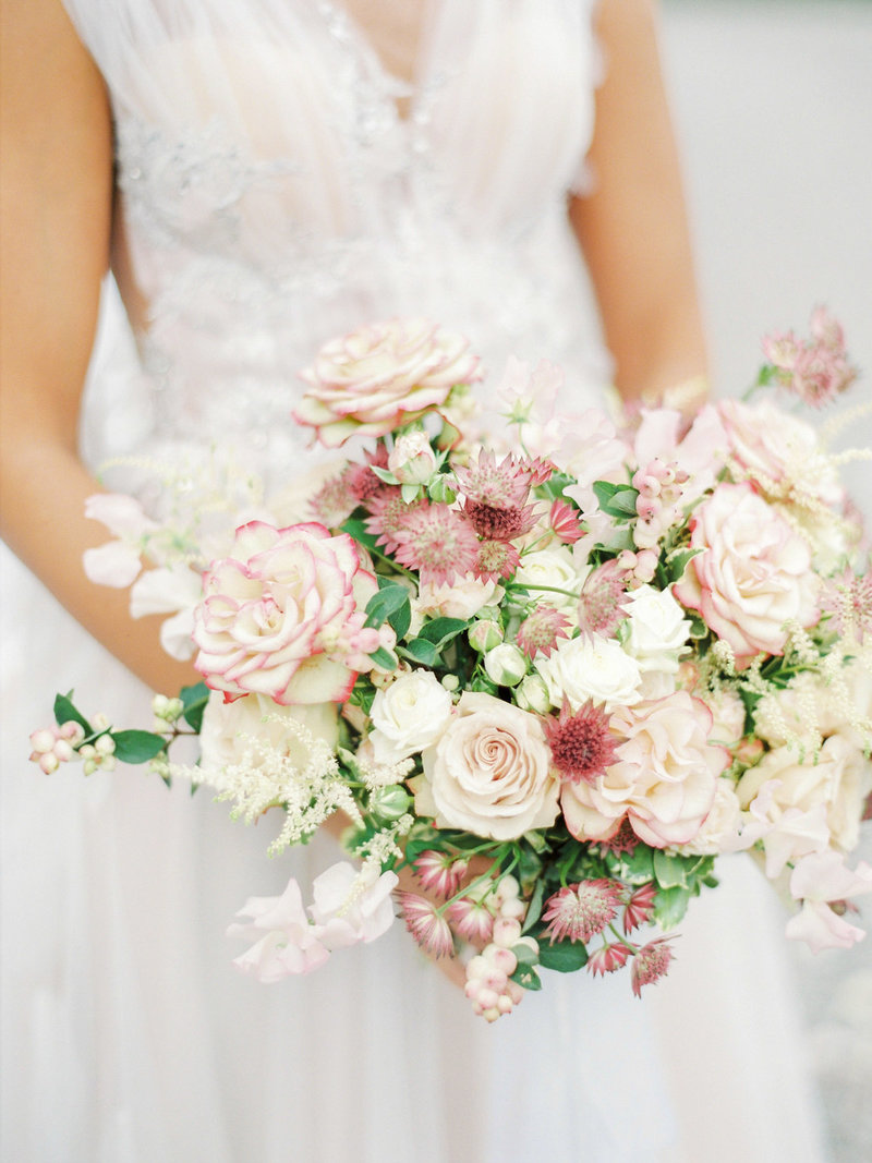 garden inspired wedding bouquet in light pink and white shades filled with roses and sweet pea designed by Stockholm floral designer Linnéa Bergqvist