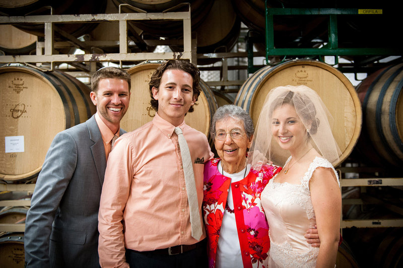 Married-Couple-with-grandmother-smiling-in-wine-celler