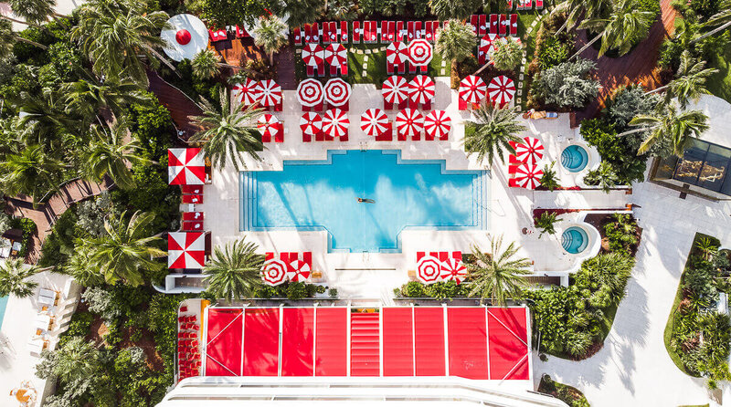 view of pool with red umbrellas - luxury travel blogger