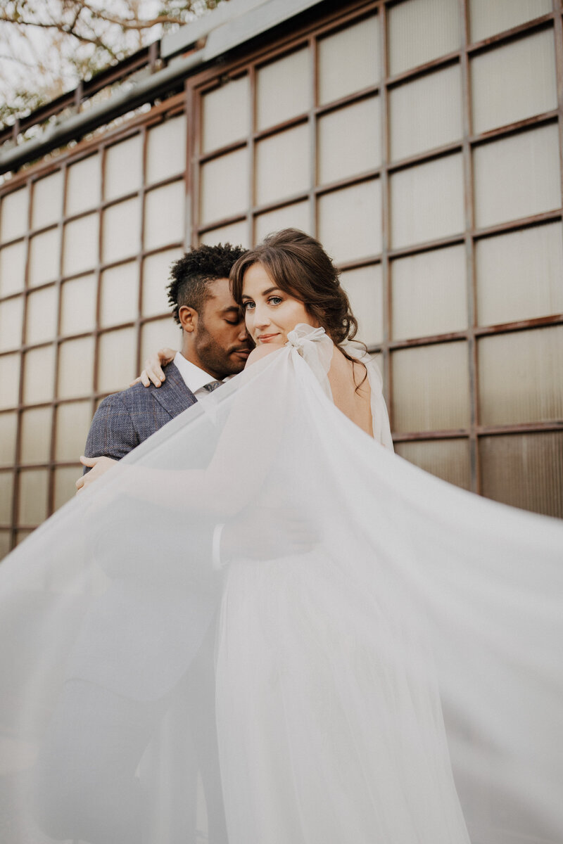 This stunning bride stares down the camera with a soft smirk as her new husband snuggles into her temple. This photos looks and feels unique with the way the bride is staring down the camera and her dress with wings follows her gaze. Photo taken by The Creative Des Moines Iowa Photographer