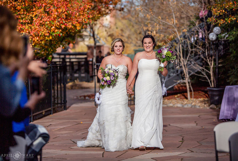 Two Brides walk into their courtyard wedding ceremony at the Golden Hotel during fall