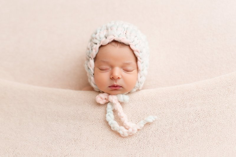 Newborn photography tucked in pink bonnet