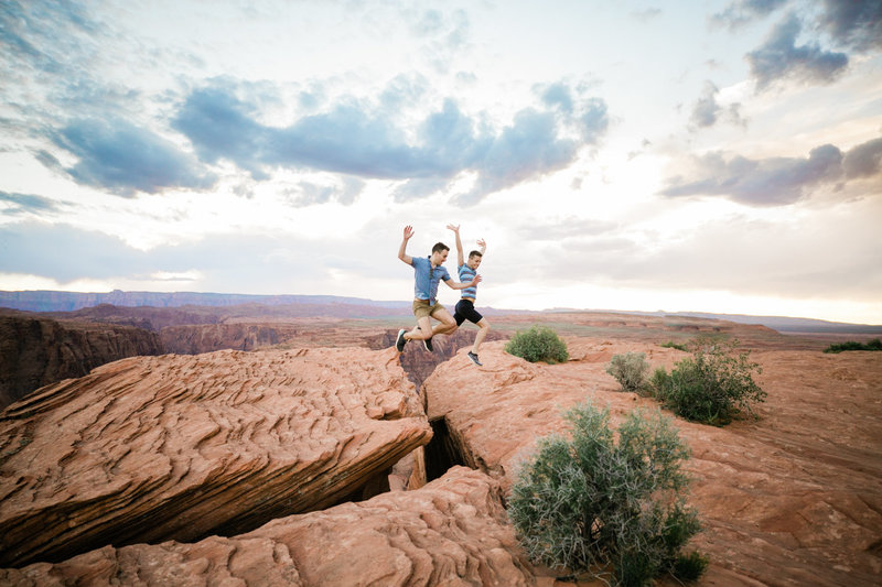 an adventurous couple leaps over a crack in the desert ground