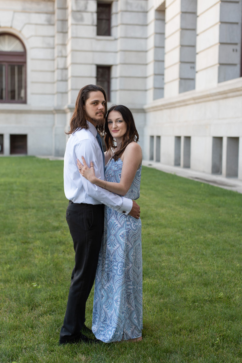 Engaged Couple in Dressy attire in front of white marble building