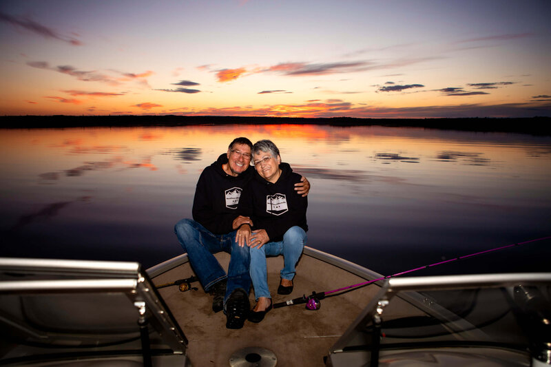 couple embraces at sunset on their boat