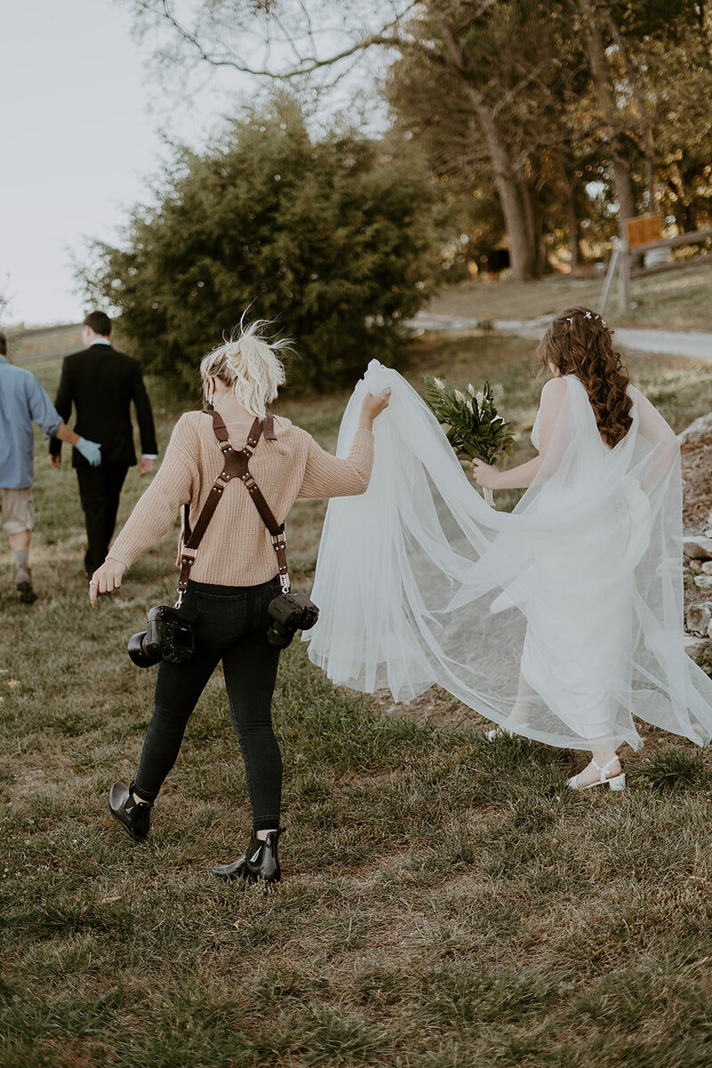 Kylee walking with a bride and holding her dress up