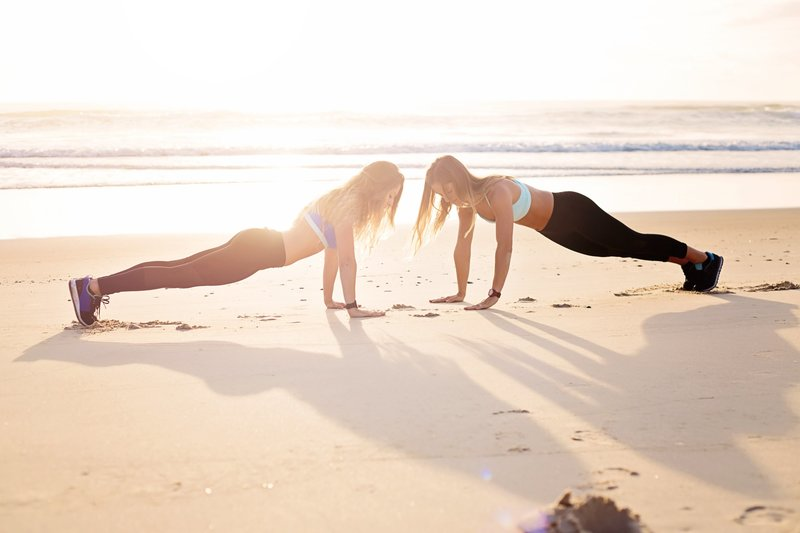 two-women-planking-at-the-seashore-1199607