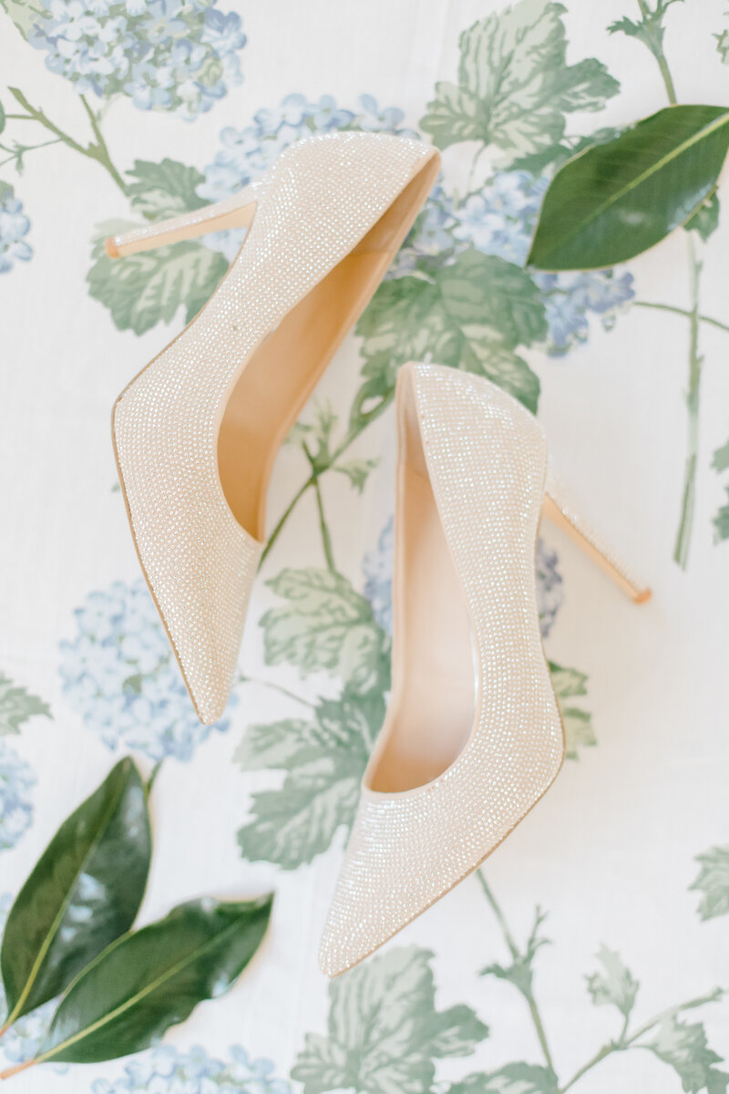 brides shoes and magnolia leaves on floral backdrop at Inn at Perry Cabin wedding in St Michaels Maryland by Costola Photography