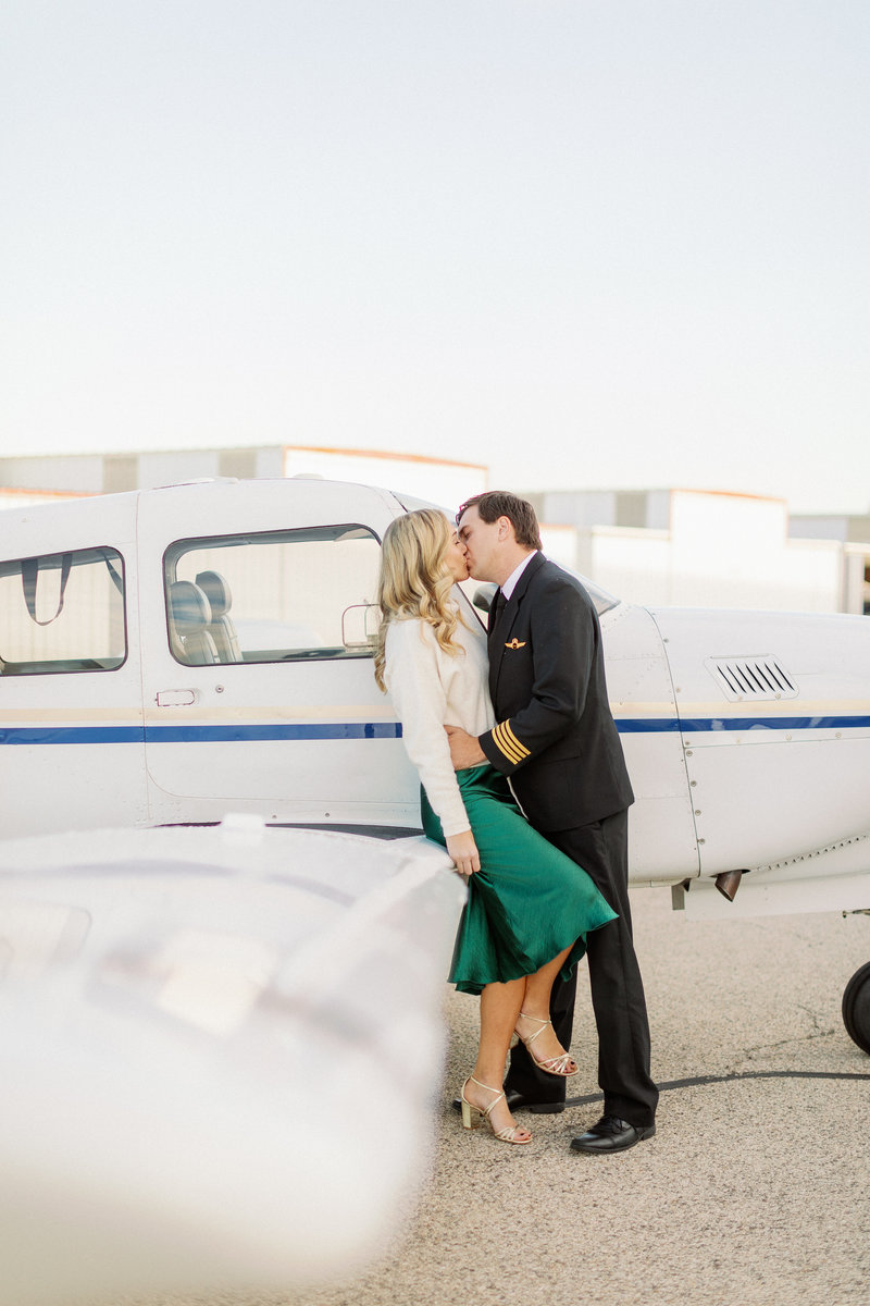 couple kissing in front of a airplane