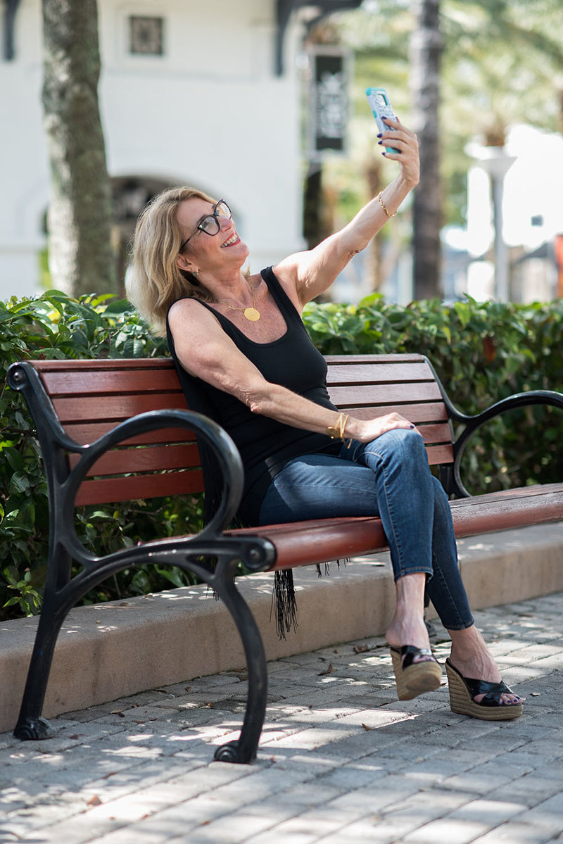 Woman sitting on bench taking a selfie
