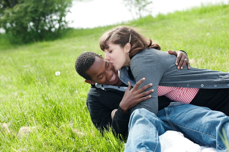 a woman falls over her fiance in the grass as she kisses his cheek during their engagement session
