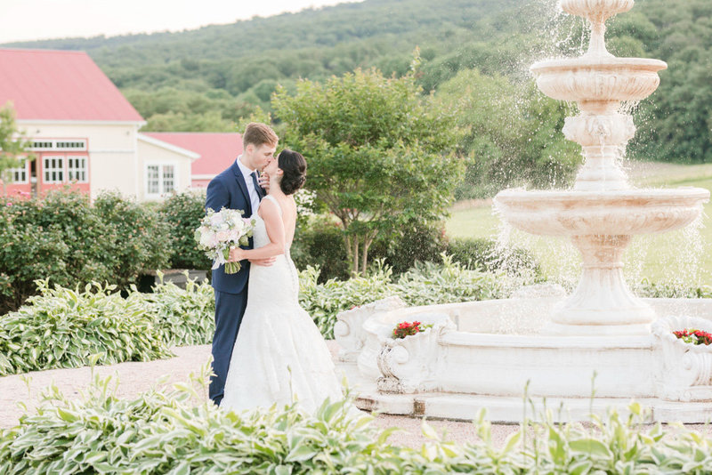 bride and groom kissing by fountain at springfield manor winery and distillery wedding by costola photography