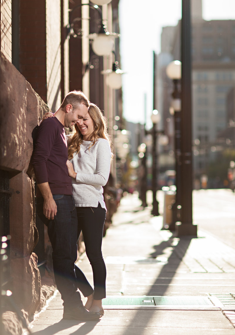 Engaged couple snuggling against historic building in downtown St. Paul MN
