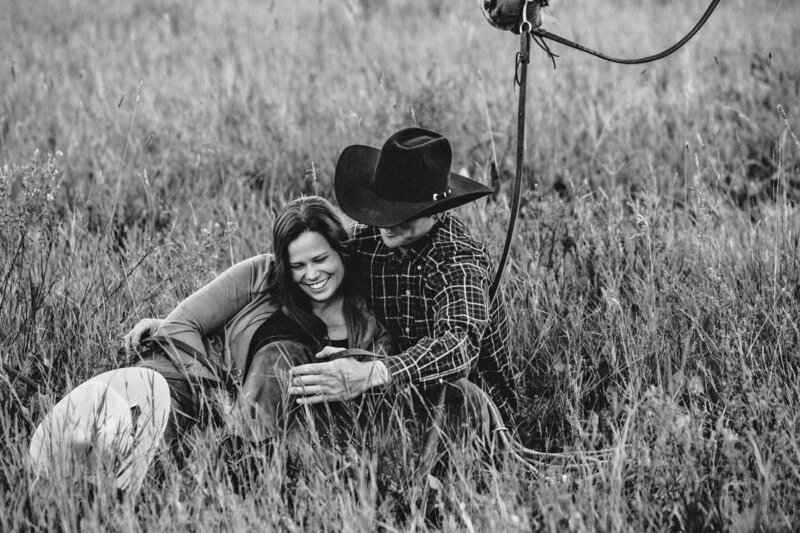 engaged couple sits in tall grass with cowboy hat and horse